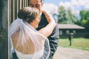 A bride with her arms around the groom