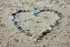 A heart shape made from stones on the beach